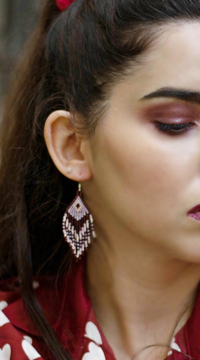 girl wears handmade fringed beaded earrings