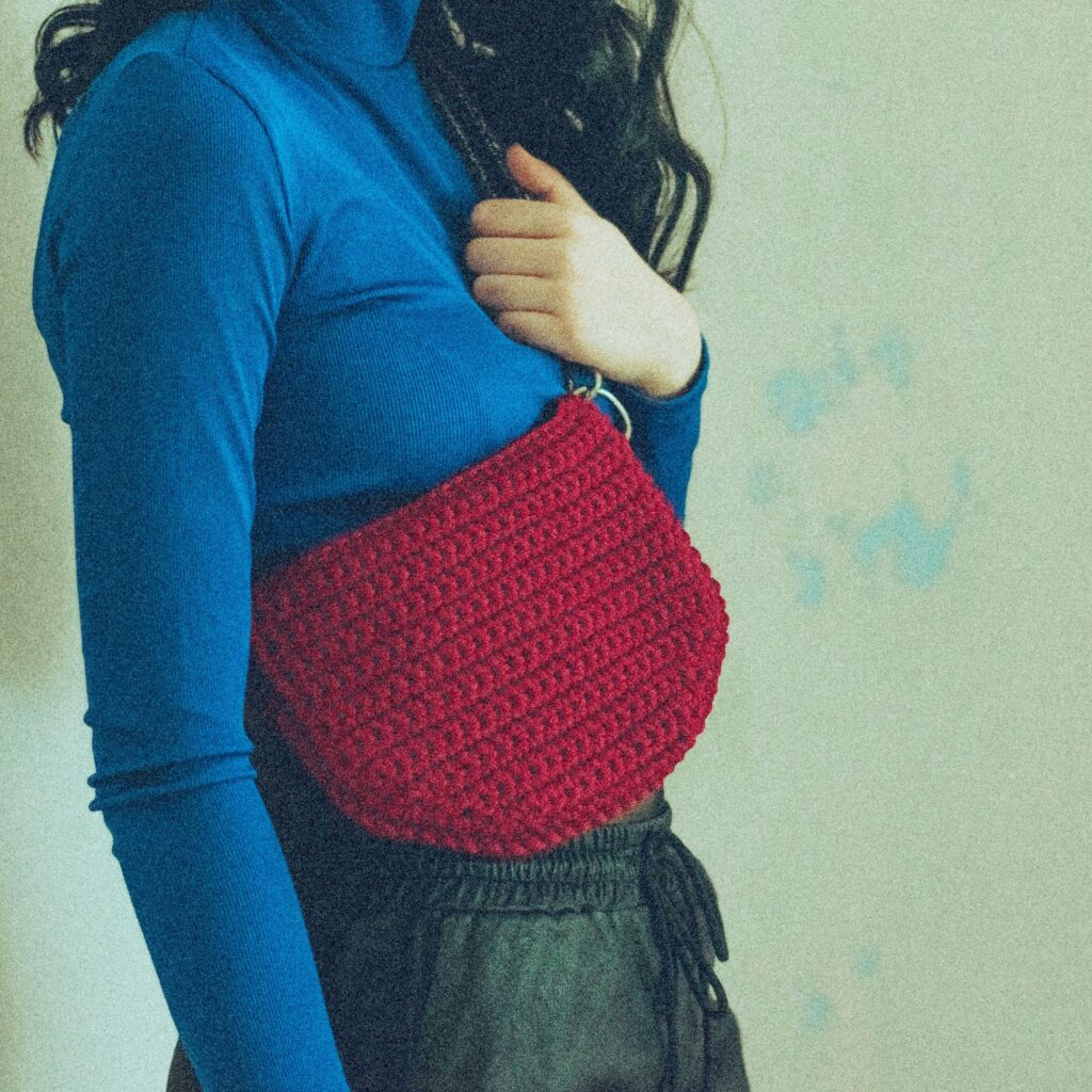 girl wearing a red handmade crochet waistbag as cross body bag