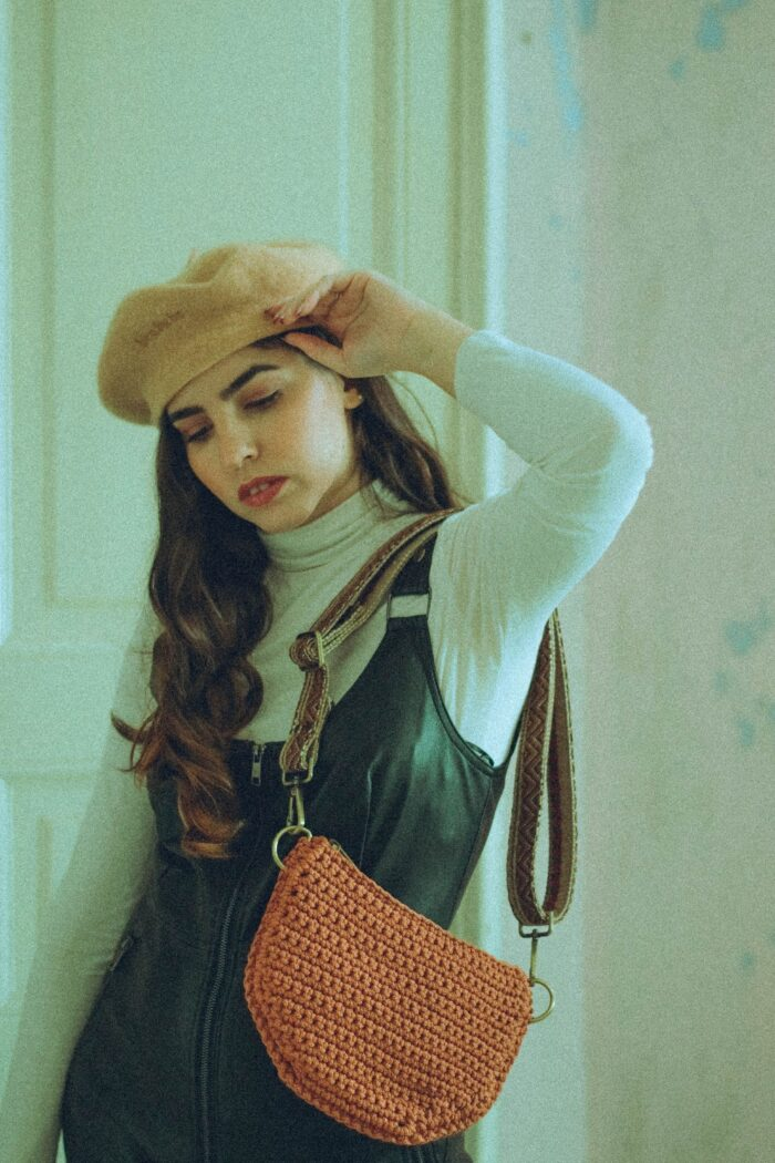 girl wearing a handmade crochet waist bag as shoulder bag