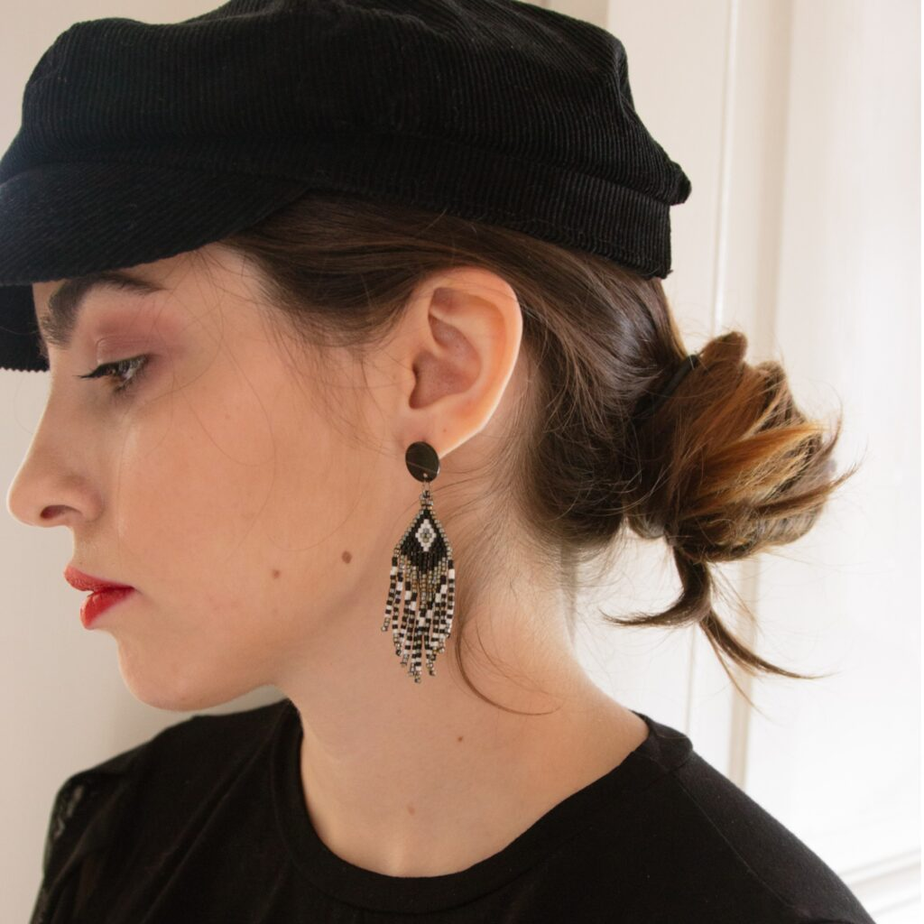 girl is wearing handmade fringed earrings in black and silver colors