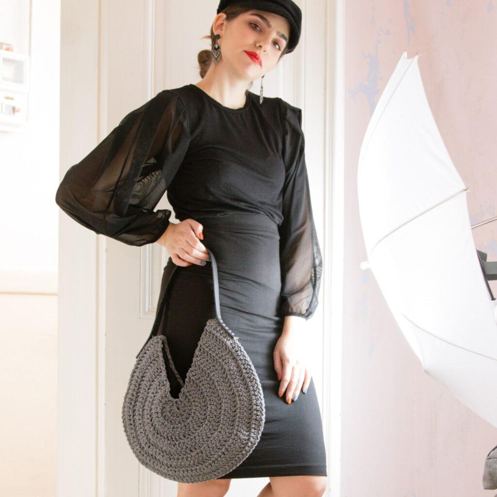 girl holds handmade crochet round bag