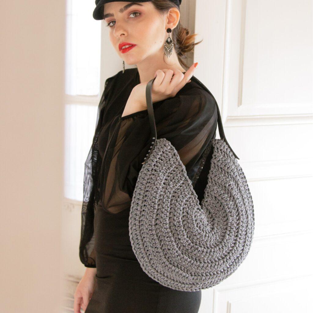girl in black wering a crochet round boho bag