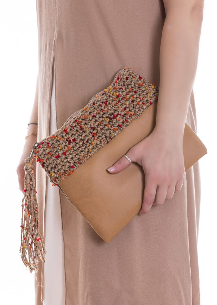 girl holding a clutch bag in eco leather and cotton yarn in sand color shades
